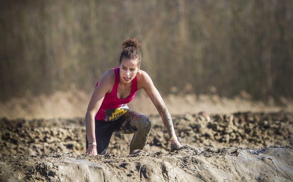 Женщина, преодолевающая препятствие - грязь