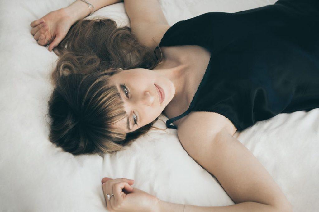 Красивая девушка, расслабленно лежащая в постели