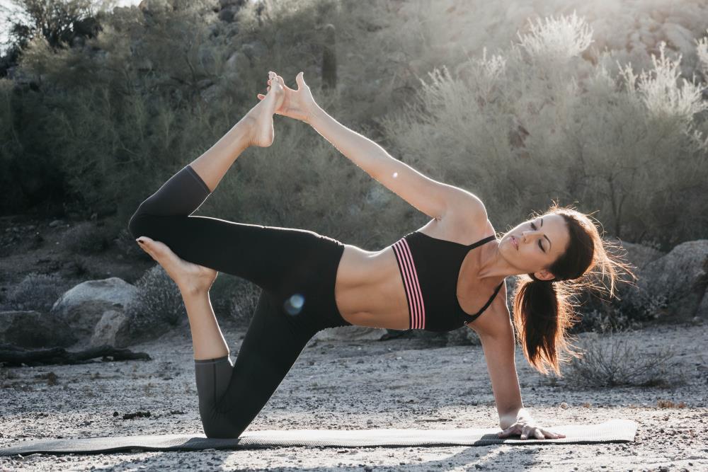 Женщина, поддерживающая тело в форме посредством йоги
