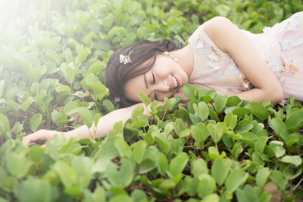 Девушка, расслабленно лежащая посреди зелени
