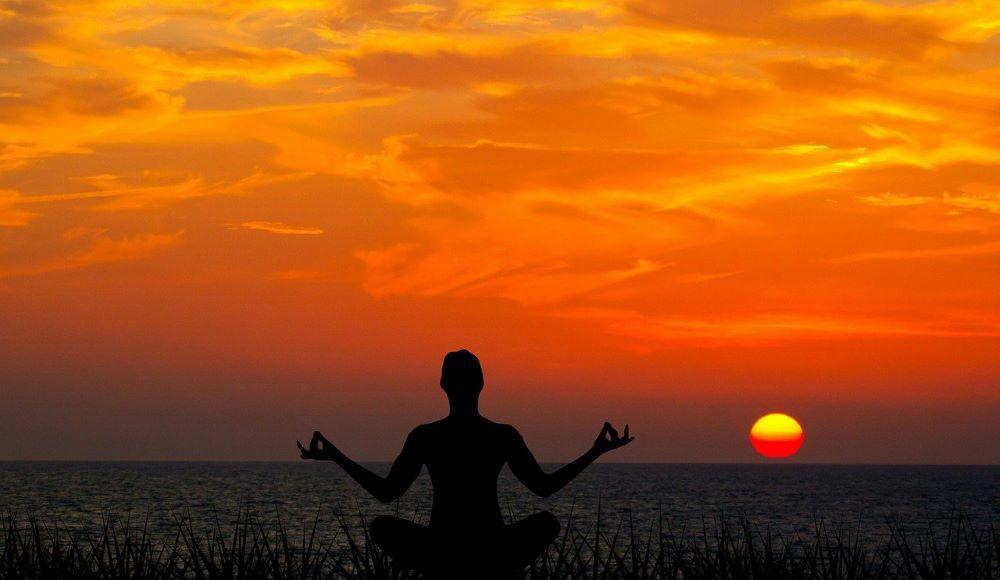 Силуэт человека во время вечерней духовной практики на закате