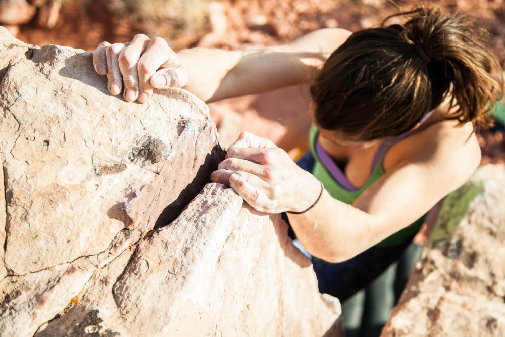 Женщина, преодолевающая трудности подъёма на скалу
