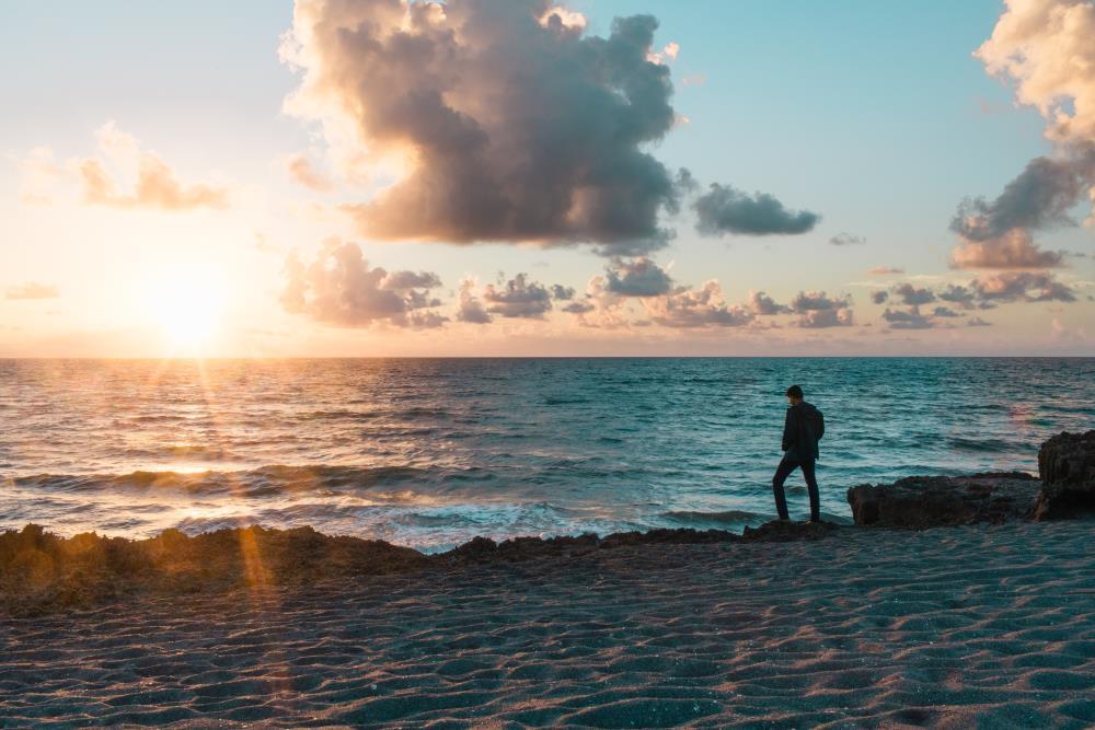 Мужчина на берегу и небо в облаках