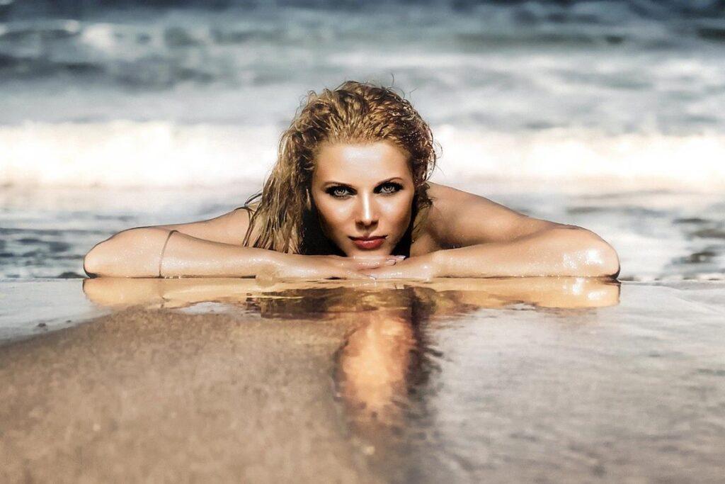 Красивая женщина лежит у моря и смотрит с любовью