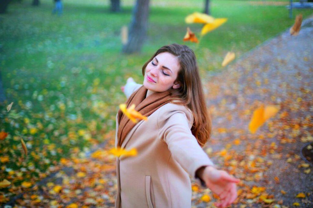 Красивая девушка наслаждается жизнью осенью