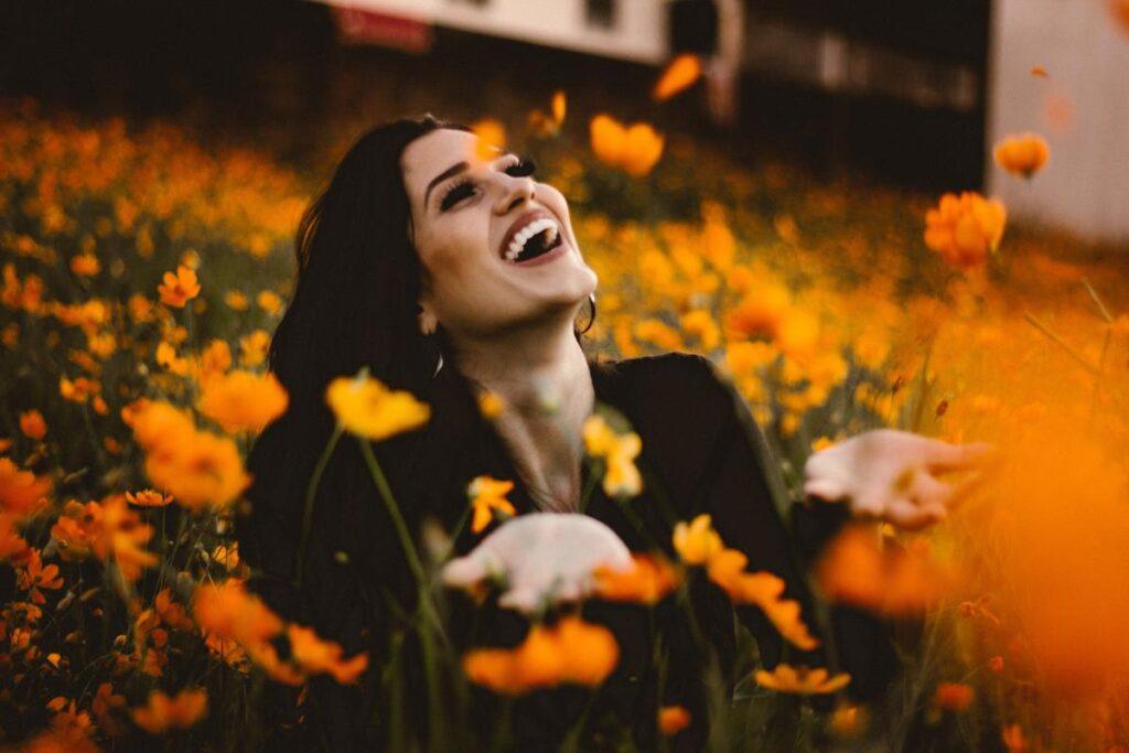 Красивая женщина среди цветов ощущает, как прекрасна жизнь