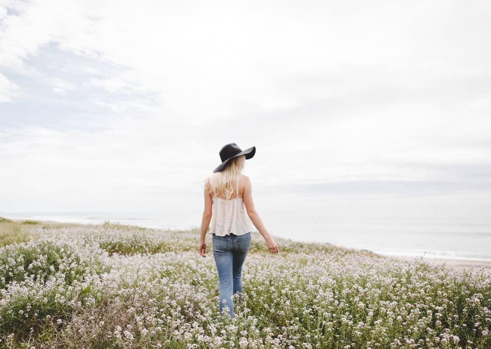 Женщина в шляпе, расслабленно идущая среди цветов
