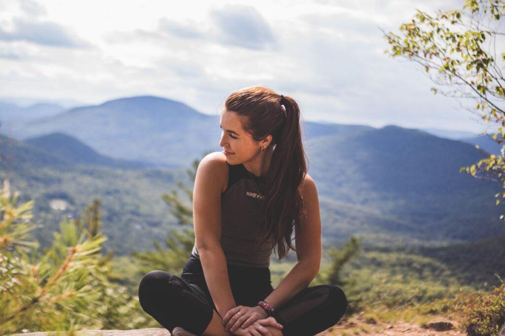 Посреди материальности: женщина сидит на фоне горного пейзажа