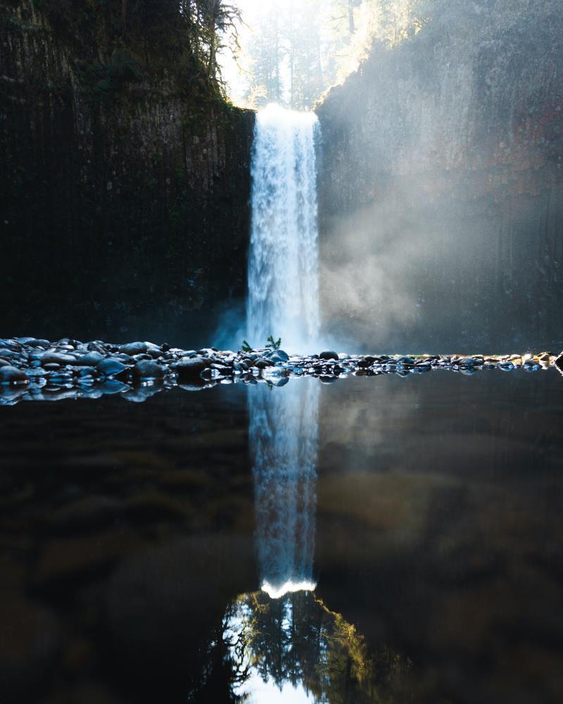 Бурный поток водопада, отражающийся в зеркальной глади воды