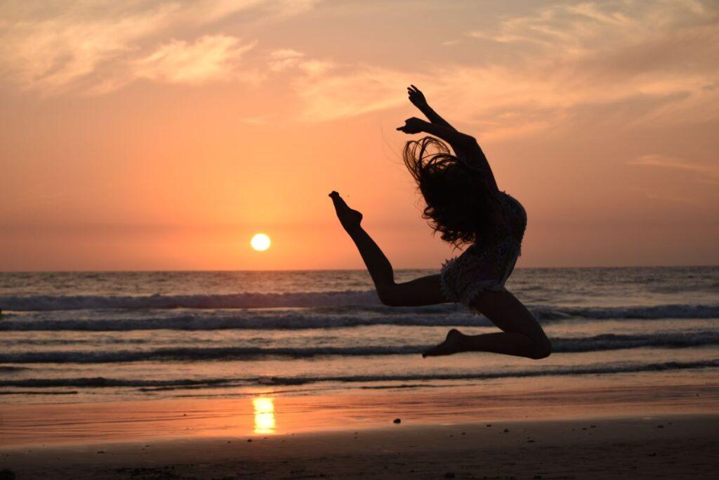 Женщина отдаётся танцу на фоне заката
