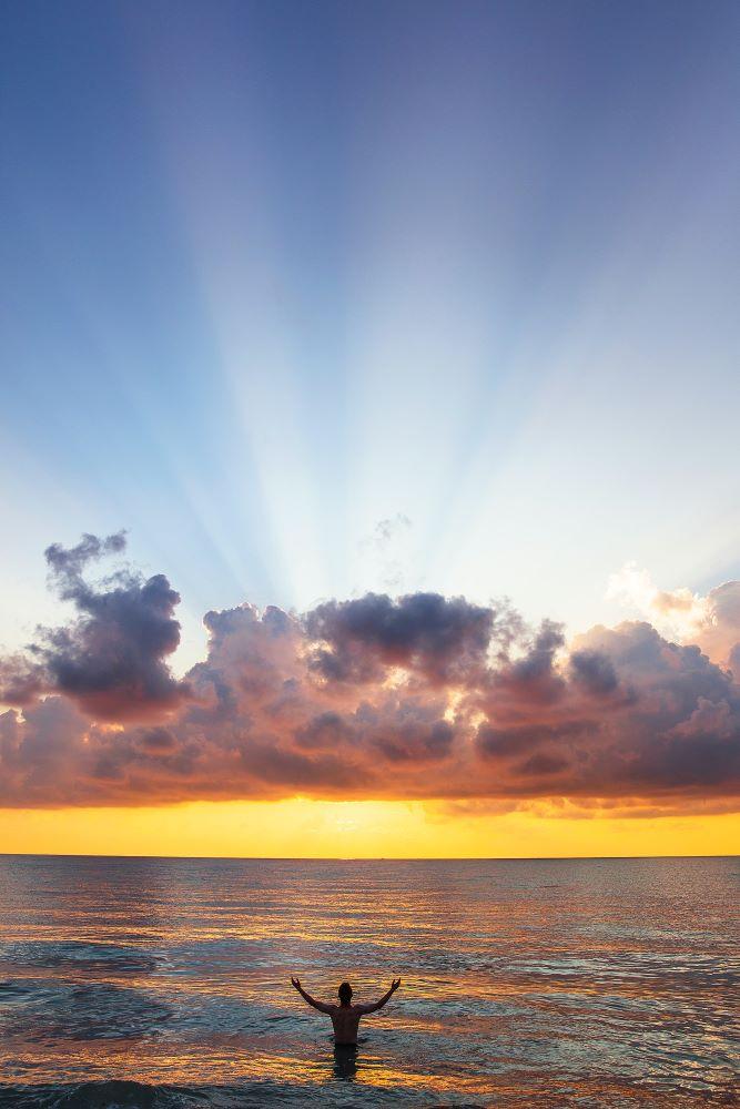 Человек погружается в океан, озарённый Солнцем