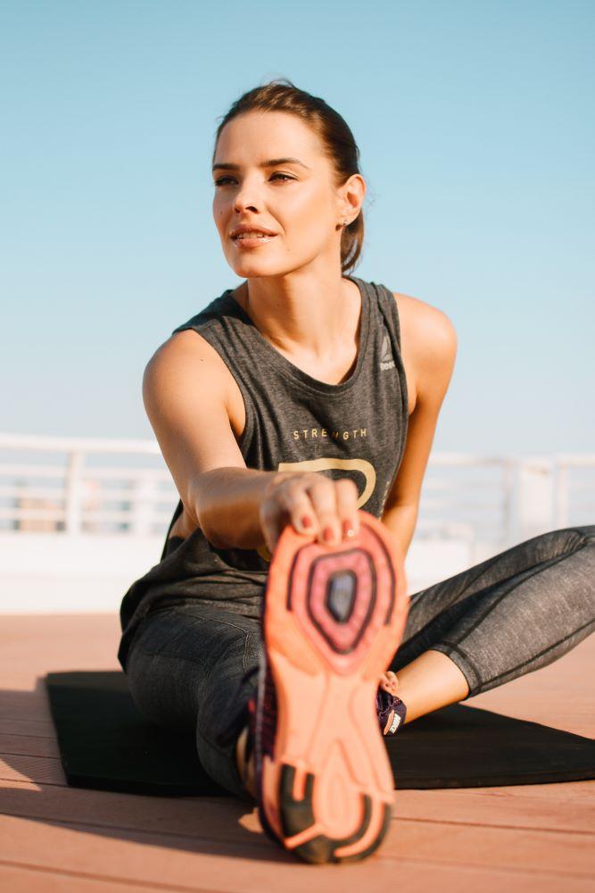 Женщина занимается фитнесом, делая упражнение на растяжку