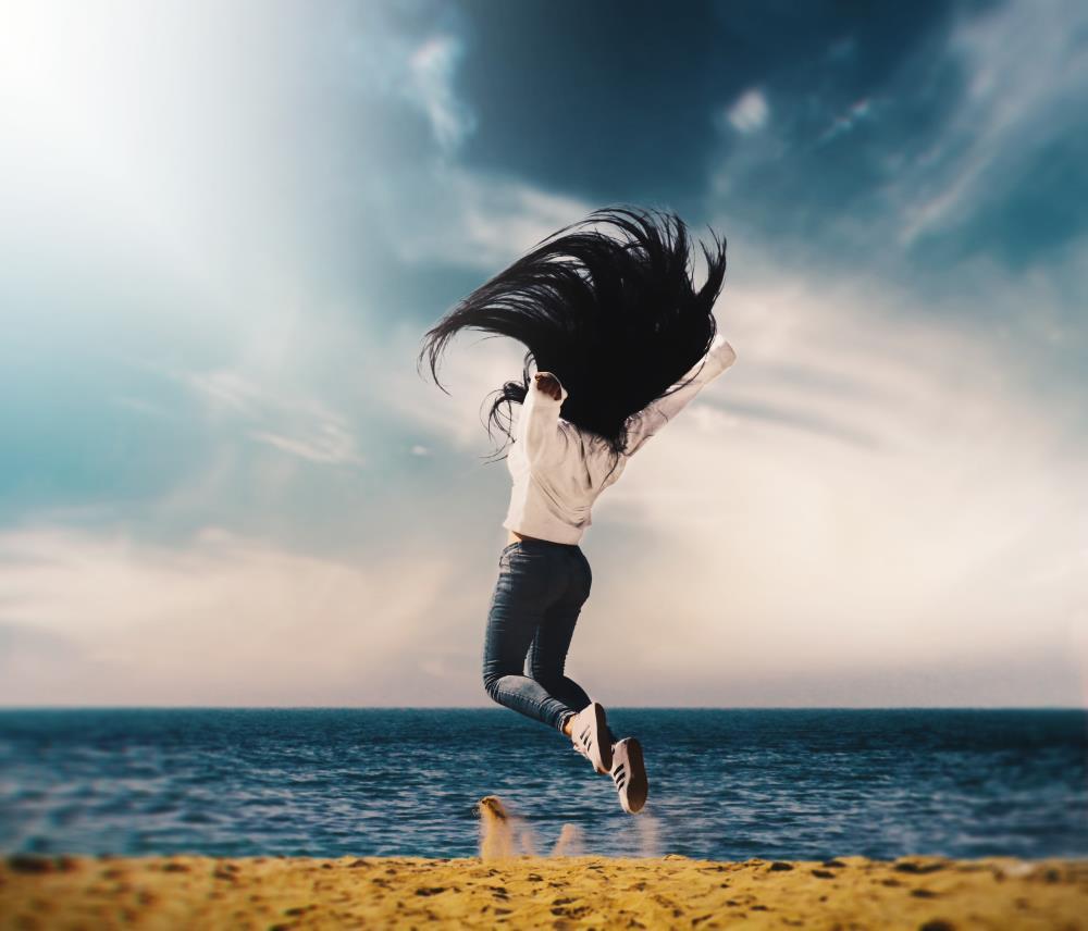 Девушка подпрыгивает на берегу океана, испытывая прилив сил