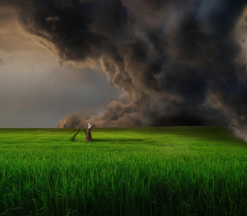 Женщина выражает эмоции, изображённые бурей, посреди зелёного поля