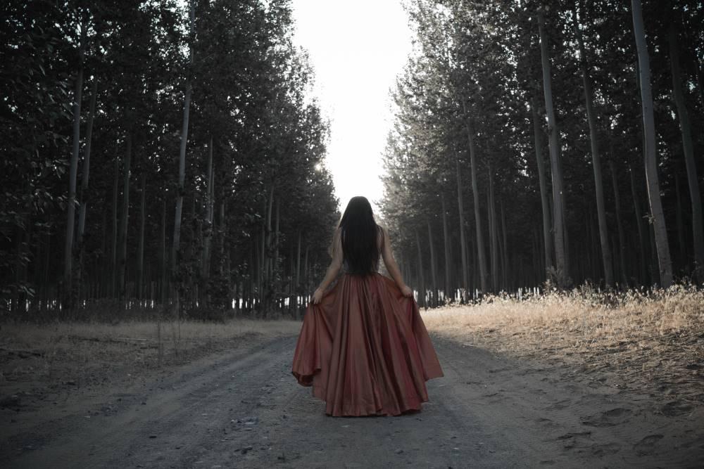 Женщина идёт через лес, символизирующий эмоциональное состояние