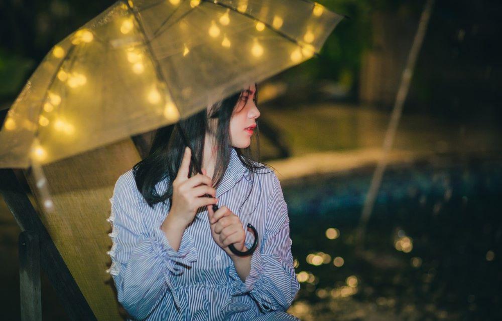 Девушка наблюдает за чем-то, стоя под зонтом