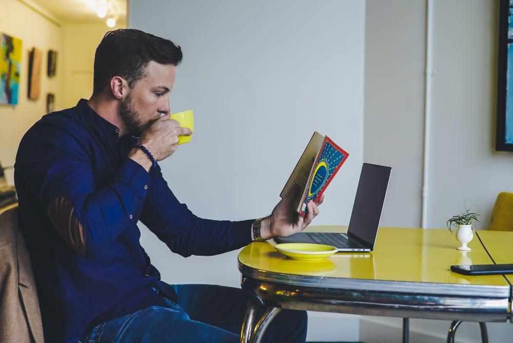 Мужчина отвлекается, читая книгу